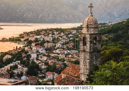 Kotor Bay and Old Town high view from above Kotor's castle of San Giovanni. Traditional house roofs, stone serbian church dome and Boka Kotorska marina by sunset.