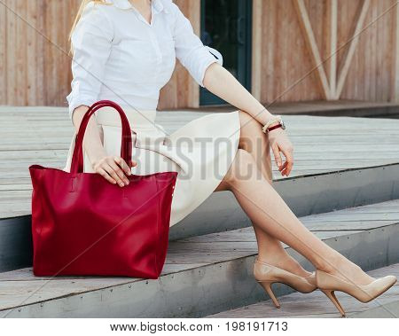 Part of body. Girl sitting on the stairs with a big red super fashionable handbag in a dress and Wide Fit Pointed Heels on a warm summer evening. Fashion. Bag.