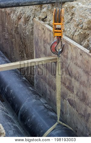 Crane Hook Hold Up Pipe In Trench