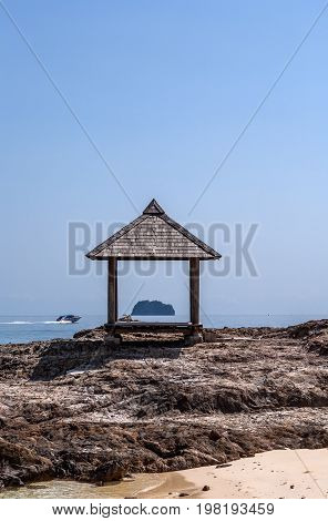 Arbor on the shore of the island of Maiton, Thailand, on a sunny day. Another island and speedboat in the background.