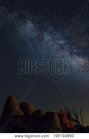 Milky Way southeastern California sky with red and brown boulders and brush at bottom