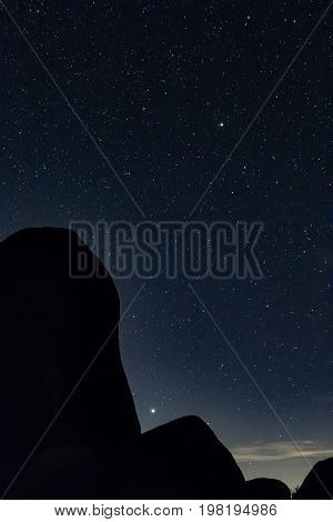 Silhouette of boulders cradling Juipter in crevice i a field of stars
