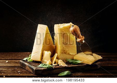 Parmesan cheese on wooden board with basil leaves. Pieces of cheese parmesan on wooden table and cheese knife. Vintage view.