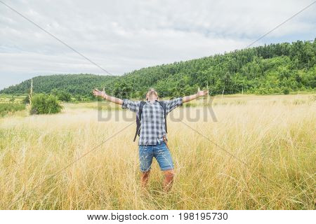 Man hiker with arms wide open in the wheat-field.