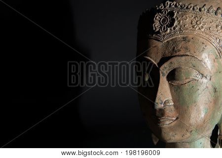 Spiritual enlightenment. Buddha statue head with copy space. Zen buddhism in the spotlight.