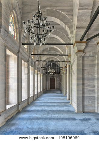 Passage in Nuruosmaniye Mosque a public Ottoman Baroque style mosque with columns arches and floor covered with blue carpet lighted by side windows located in Shemberlitash Fatih Istanbul Turkey