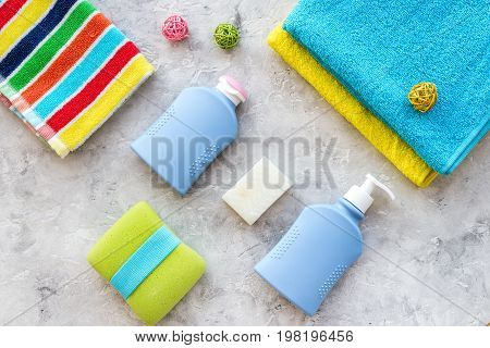 Bath accessories. Towels, soap, shampoo, washclothes on grey background top view