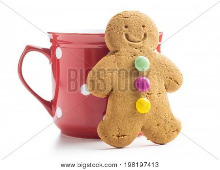 Gingerbread man leaning against a cup isolated on white background. Xmas gingerbread.
