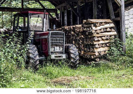 An old tractor front view in germany countryside old abandoned barn firewood wood stacked