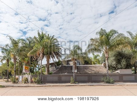 OTAVI NAMIBIA - JUNE 20 2017: A guest house shaded by many palm trees in Otavi in the Otjozondjupa Region of Namibia