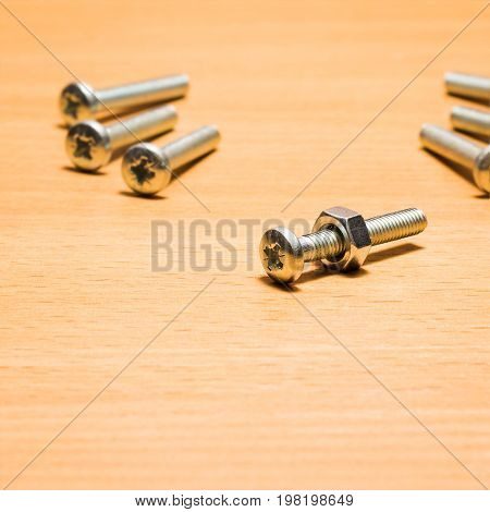 Screw with a nut on it on a wooden background fastening tools are very durable and reliable with thread