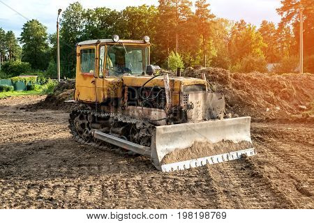 Old excavator working clearing land at sunset of a Sunny day. The horizontal frame.