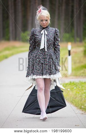 young blond woman holds the broken umbrella in hand and looks sad