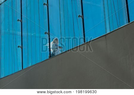Blond Woman With Bags In Sunshine On Oslo Opera House