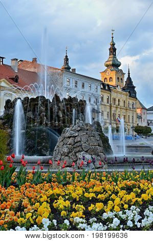 Spring city centre in Banska Bystrica. Historical buildings in Slovakia. Sunset in Square of Slovak National Uprising with blooming flowers. Splashing stone fountain