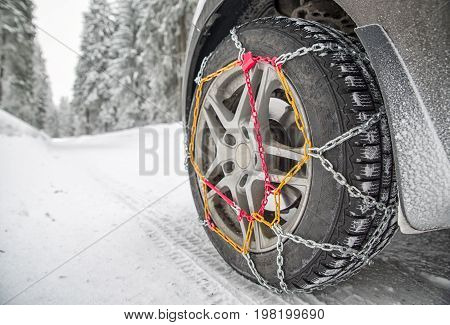 Snow chains on tire. Detail of wheel in winter forest