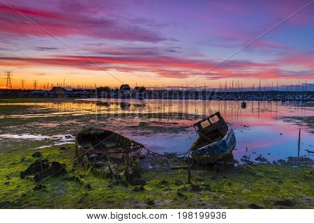 Derelict boats in the backwaters of Holes Bay Poole Harbour at low tide