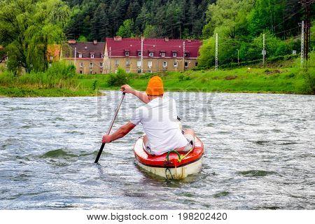 Man in canoe on river Vah in town Ruzomberok Slovakia