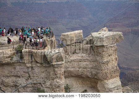 ARIZONA, UNITED STATES - JULY 23 , 2017:  Tourists on the top the Grand Canyon, a steep-sided canyon carved by the Colorado River in Arizona, United States.
