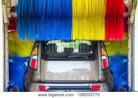 Car in automatic carwash between colorful brushes