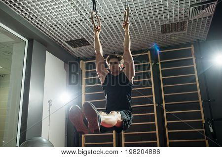 Fitness Handsome Man Doing Dipping Exercise Using Rings In The Gym. Sport