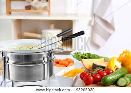 Cheese fondue in pot on kitchen table