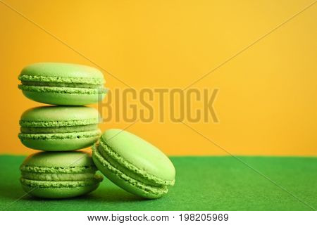 Tasty macarons on green surface against color background
