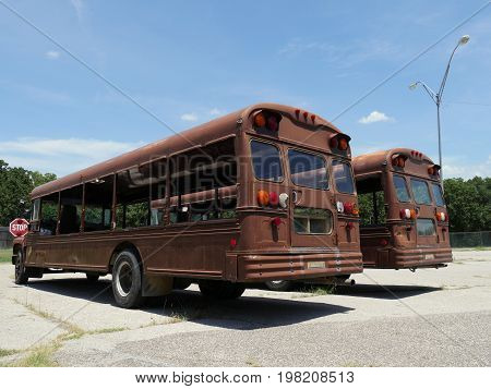 Vintage rustic tour buses without the glass windows at a parking lot
