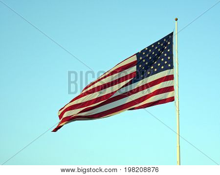 Flag of the United States of America waving in the wind from its post, with light blue background