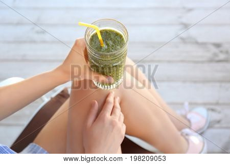Woman holding glass with tasty fresh smoothie in cafe