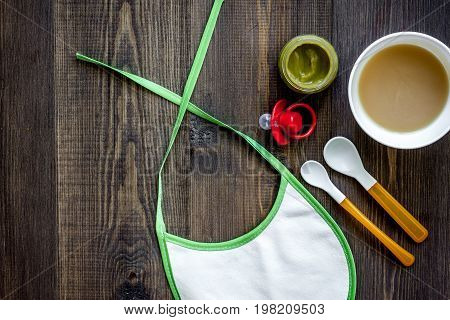 Preparing to feed baby. Puree, spoon and bib on dark wooden table background top view.