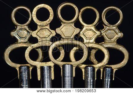 Five Antique Brass Pocket Watch Keys Standing in the Darkness