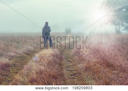 Traveler on autumn foggy meadow looks at on bright sunlight. Cold foggy morning on autumn meadow on outdoor