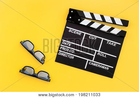 Watching film. Clapperboard on yellow background top view.