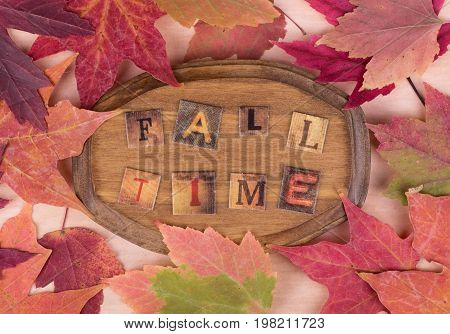 Wood plaque with fall time text surrounded by colorful autumn leaves