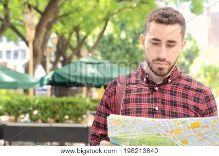 Portrait of a young handsome tourist man looking at a map. Tourism concept. Outdoors.