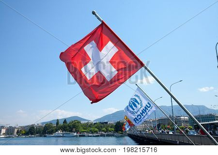 GENEVA SWITZERLAND - JUNE 19 2017: Swiss flag and UNHCR flags near leman lake in Geneva. The UNHCR is the agency of the United Nations in charge of handling refugees crises.