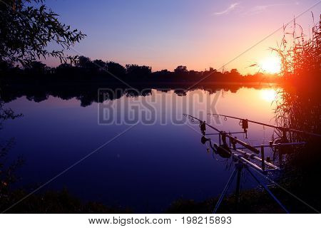 Angler catches fish during a beautiful sunset.