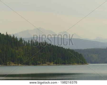Local resevoir with forest fire smoke that is occluding the mountain range in the distance.