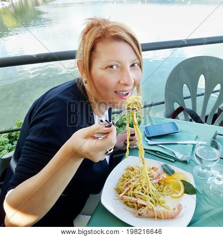 Middle-aged Caucasian woman eating seafood pasta in italian restaurant.