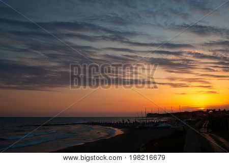 Orange sunset above the sea at Marina di San Nicola Lazio Italy.