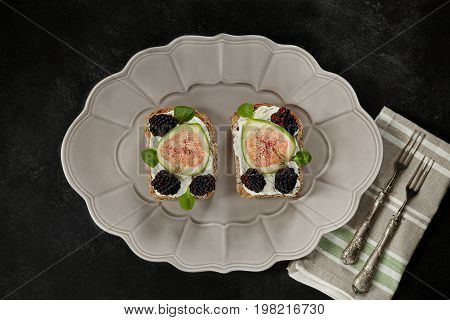 Plate with toasts made by wholemeal bread cream cheese blackberries and figs flat lay.