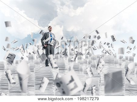 Confident businessman in suit standing among flying paper documents and looking away with cloudly skyscape on background. Mixed media.