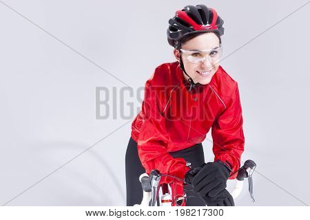 Cycling Ideas And Concepts. Portrait of Caucasian Female Cyclist Equipped in Cycling Outfit and Posing With Road Bike In Studio. Horizontal Shot