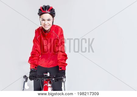 Cycling Ideas And Concepts. Portrait of Caucasian Female Cyclist Equipped in Cycling Outfit and Posing With Road Bike In Studio.Horizontal Image Composition