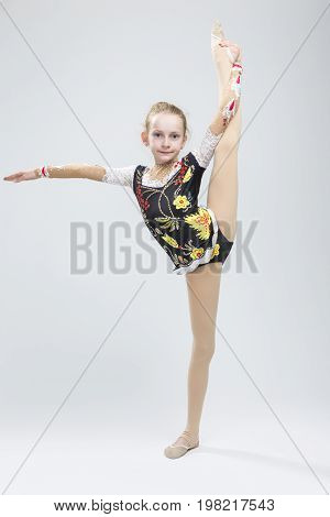 Sport concepts and Ideas. Young Caucasian Female Rhythmic Gymnast Athlete In Professional Competitive Suit Doing Vertical Split Exercise While Posing in Studio Against White. Vertical Image