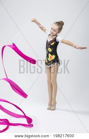 Portrait of Caucasian Female Rhythmic Gymnast In Professional Competitive Suit Doing Artistic Ribbon Spirals Exercises in Studio On White. Vertical Image Orientation