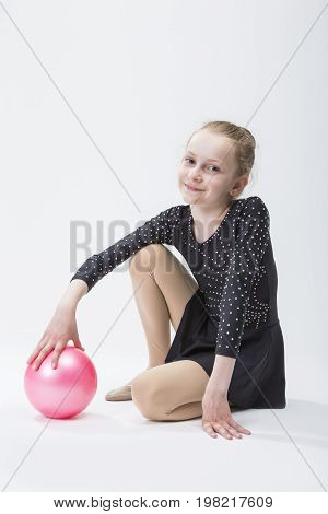 Caucasian Female Rhythmic Gymnast In Professional Competitive Black Sparkling Suit Posing With Ball in Studio On White.Horizontal Image Composition