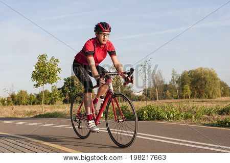 Sport and Cycling Concepts and Ideas. Male Caucasian Road Cyclist During Ride on Bike Outdoors. Completely Equipped in Professional Outfit.Horizontal Image
