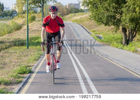 Sport and Cycling Ideas. Portrait of Professional Male Cyclist Doing Uphill on Road Bike. Fully Equipped in Professional Outfit. Horizontal Image